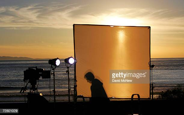 A silhouette is visible on a light diffuser at a news crew's set as the sun sets over the ocean while rescuers continue searching for survivors and...