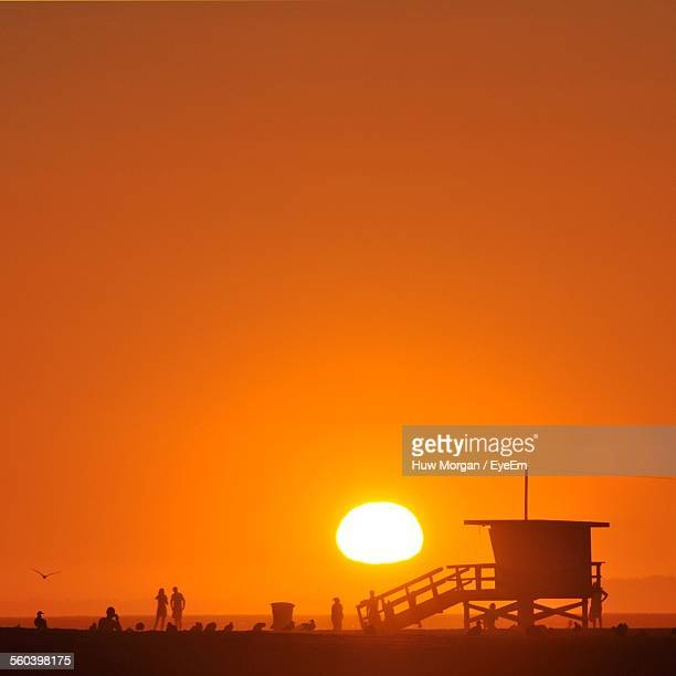 Silhouette Lifeguard Hut On Beach By Clear Sky During Sunset