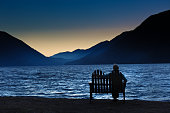 Lonely person woman sitting in front of Lake Crescent in Olympic National Park at sunrise. A melancholic scene. Photographed in horizontal format with copy space.