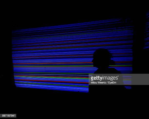 Silhouette Man Against Illuminated Colorful Neon Lights