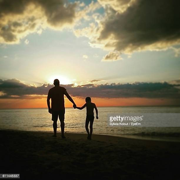 Silhouette Man And Kid Holding Hands On Beach