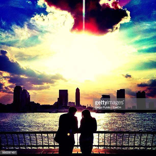 Silhouette Man And Woman Standing By River With City Skyline In Background During Sunset