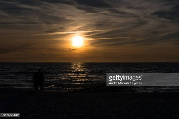 Silhouette Man And Woman Standing On Beach Against Sky During Sunset