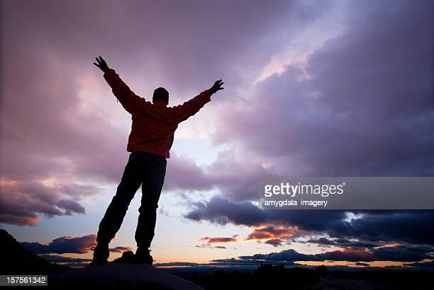 silhouette man arms raised into sunset sky clouds