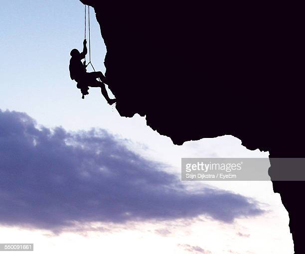 Silhouette Man Climbing Mountain Against Sky At Sunset