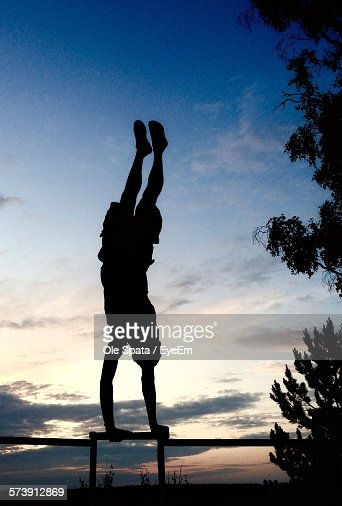 Silhouette Man Doing Handstand On Railing Against Sky During Sunset