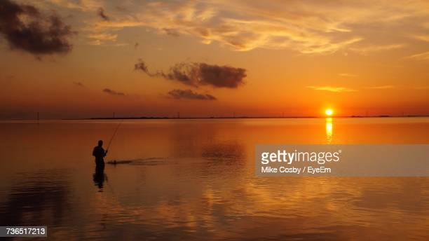 Silhouette Man Fishing On Beach Against Sky During Sunset