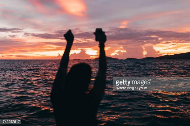 Silhouette Man Holding Drink With Arms Raised During Sunset Against Sea