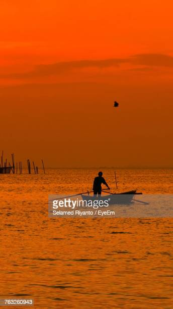Silhouette Man In Boat On Sea Against Dramatic Sky During Sunset