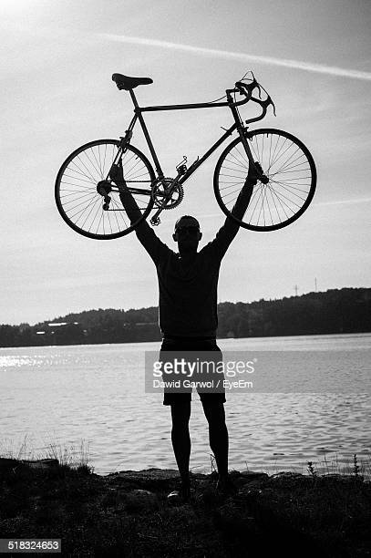 Silhouette Man Lifting Bicycle Against Lake