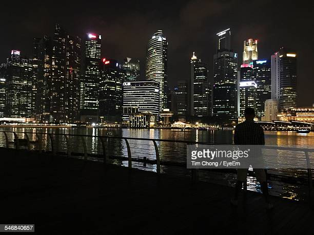 Silhouette Man Looking At Illuminated Skyline From Marina Bay Sands Boardwalk At Night