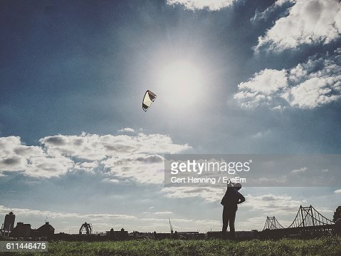 Silhouette Man Looking At Parachute Flying In Sky On Sunny Day