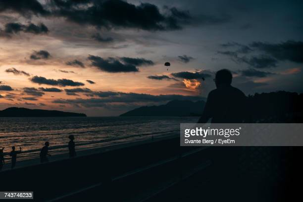 Silhouette Man Looking At Sea While Standing On Promenade Against Sky During Sunset