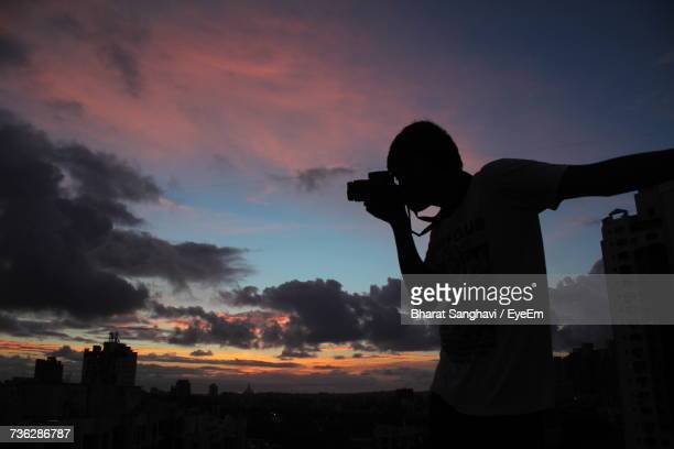 Silhouette Man Photographing Cityscape Against Sky During Sunset