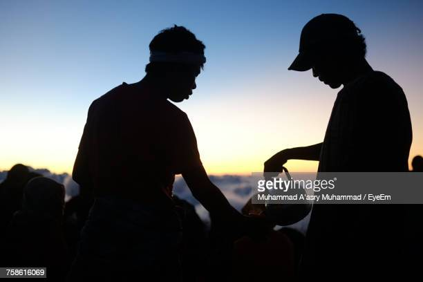 Silhouette Man Pouring Coffee For Hiker Against Sky During Sunset