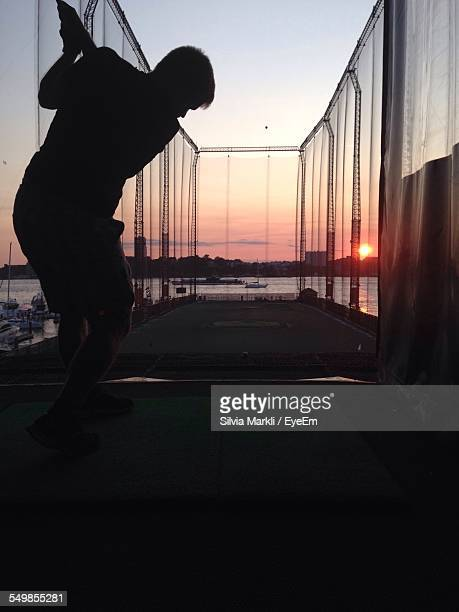 Silhouette Man Practicing Golf Swing In Driving Range During Sunset