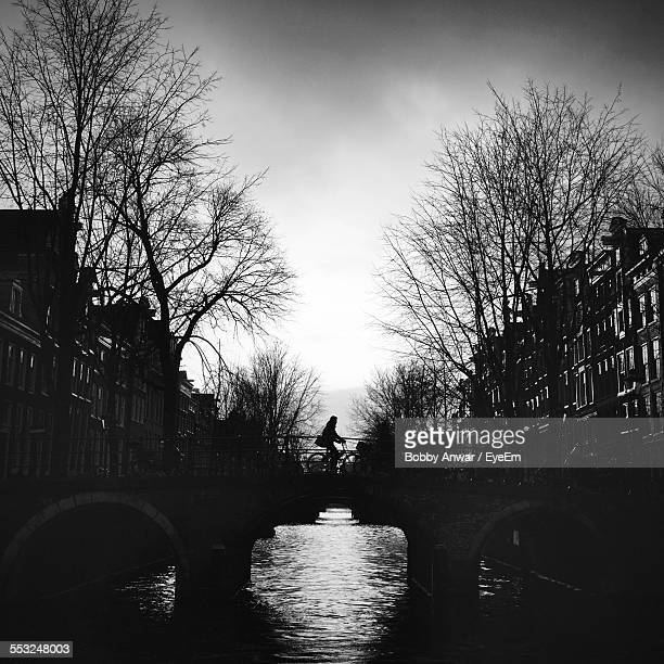 Silhouette Man Riding Bicycle On Bridge Over River In City Against Sky At Dusk