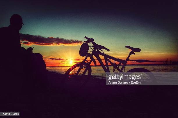 Silhouette Man Smoking By Bicycle At Beach During Sunset