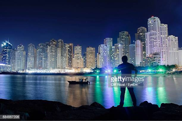 Silhouette Man Standing At Lakeshore Against Illuminated Cityscape