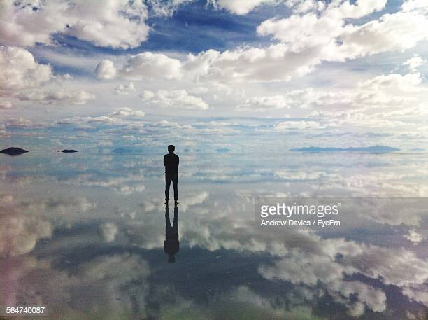 Silhouette Man Standing On Beach Against Cloudy Sky