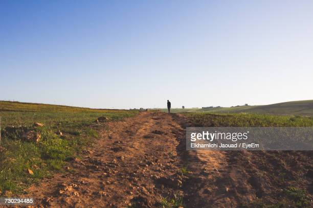 Silhouette Man Standing On Landscape Against Sky