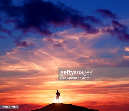 Silhouette Man Standing On Mountain Against Cloudy Sky During Sunset