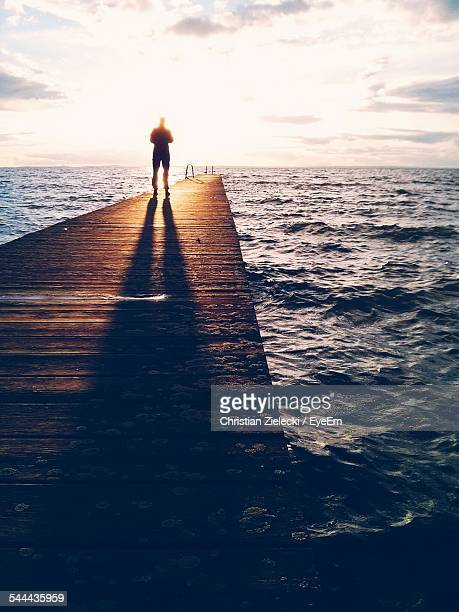 Silhouette Man Standing On Pier Over Sea During Sunset