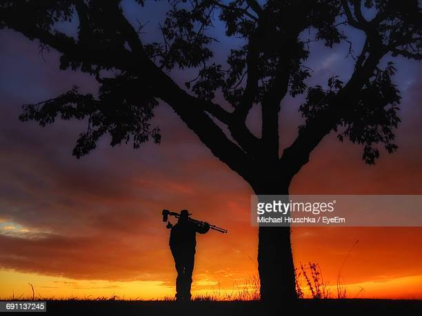 Silhouette Man Standing With Tripod By Tree Against Orange Sky
