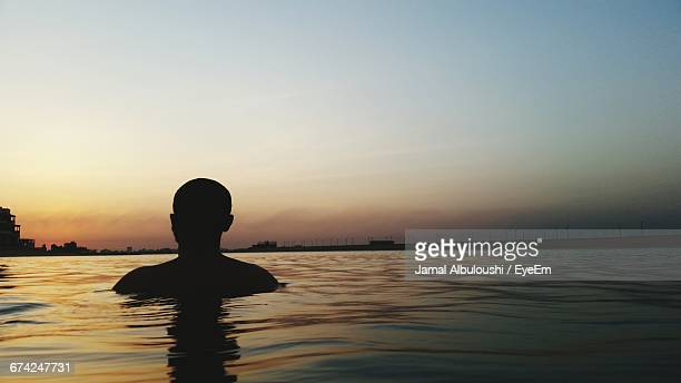 Silhouette Man Swimming In Lake Against Sky