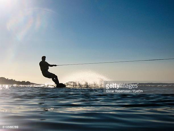 Silhouette man wakeboarding in sea