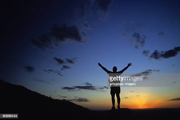 silhouette man with arms raised into sunset sky landscape