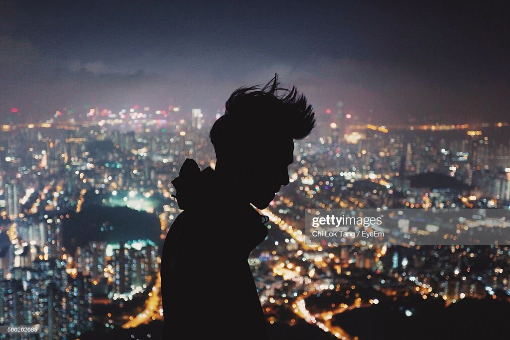 Silhouette Man With Illuminated Cityscape In Background At Night : Stock Photo