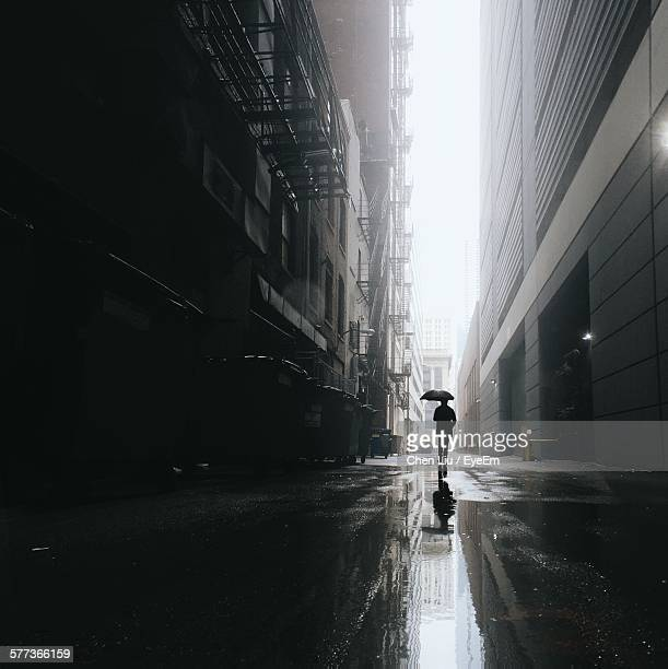 Silhouette Man With Umbrella Walking On Wet Street Amidst Buildings In City