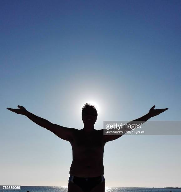 Silhouette Mature Man With Arms Outstretched Standing Against Clear Sky