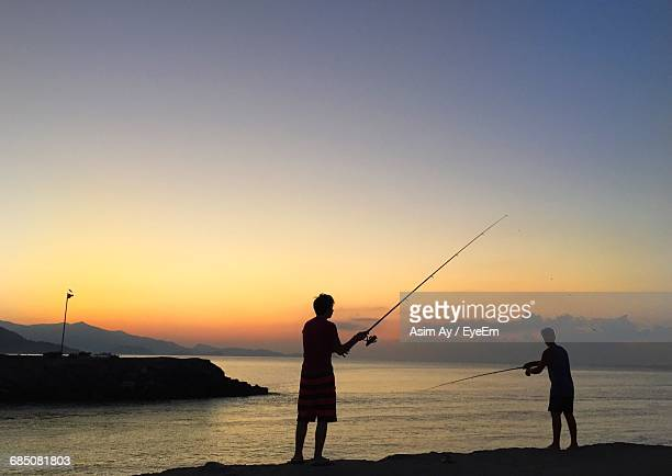 Silhouette Men Fishing In Sea Against Clear Sky