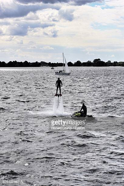 Silhouette Men Flyboarding And Jet Skiing On Sea Against Cloudy Sky