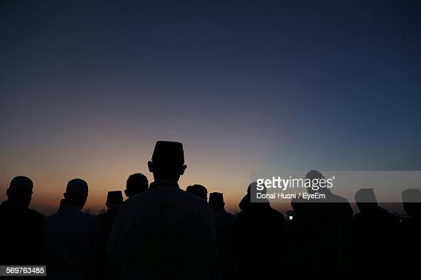 Silhouette Men Standing On Field At Sunset During Eid-Ul-Fitr