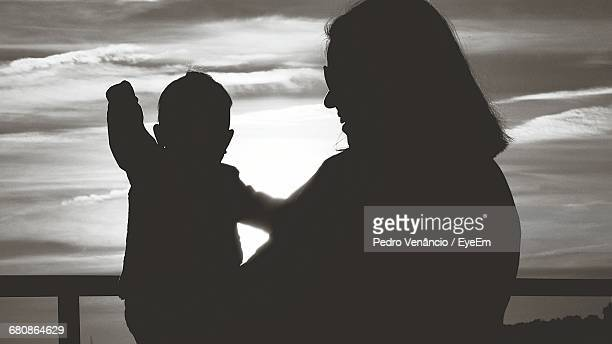 Silhouette Mother And Daughter Against Cloudy Sky During Sunset