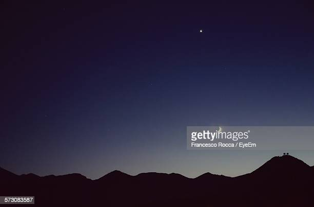 Silhouette Mountains With Moon And Star Against Clear Sky At Night