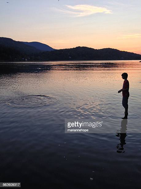 Silhouette of a boy fishing at night in mid summer, hof, norway