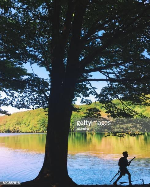 Silhouette of a boy walking by a lake