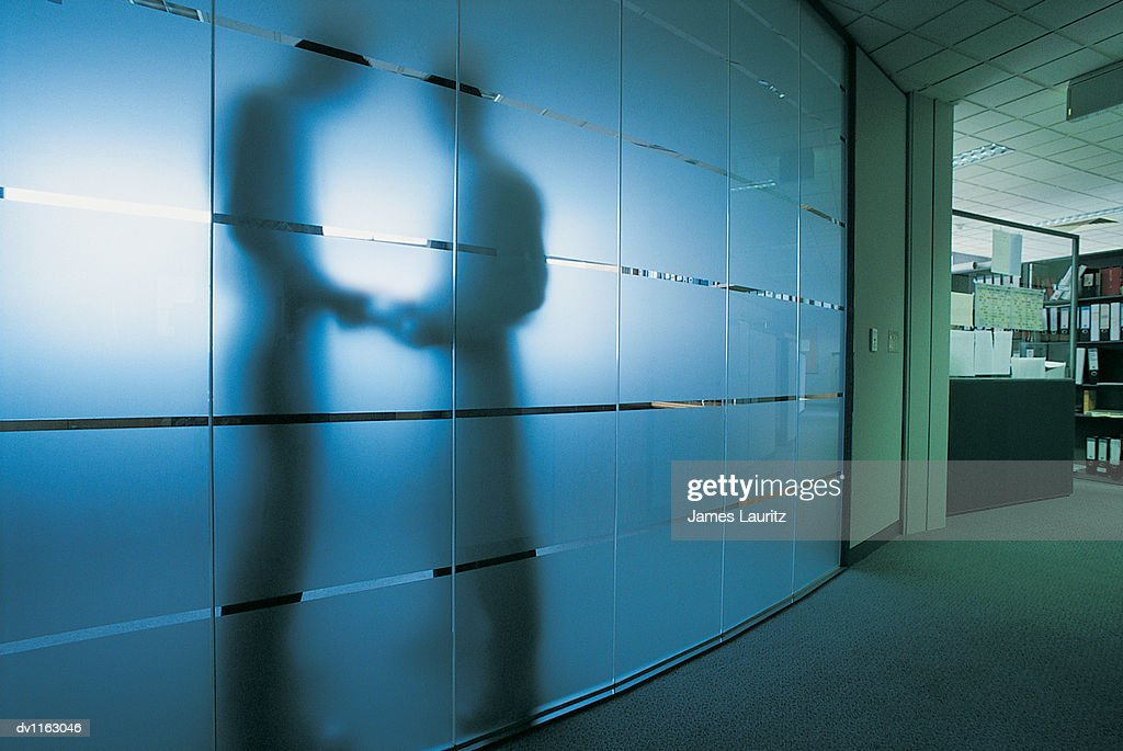 Silhouette of a Businessman Standing Behind a Frosted Glass Window in An Open Plan office Receiving a Bribe From Another Businessman : Stock Photo