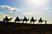 Landscape. Silhouette of a camel caravan in the desert, beautiful morning sky as background. Created in Dunhuang, China, 07/07/2018