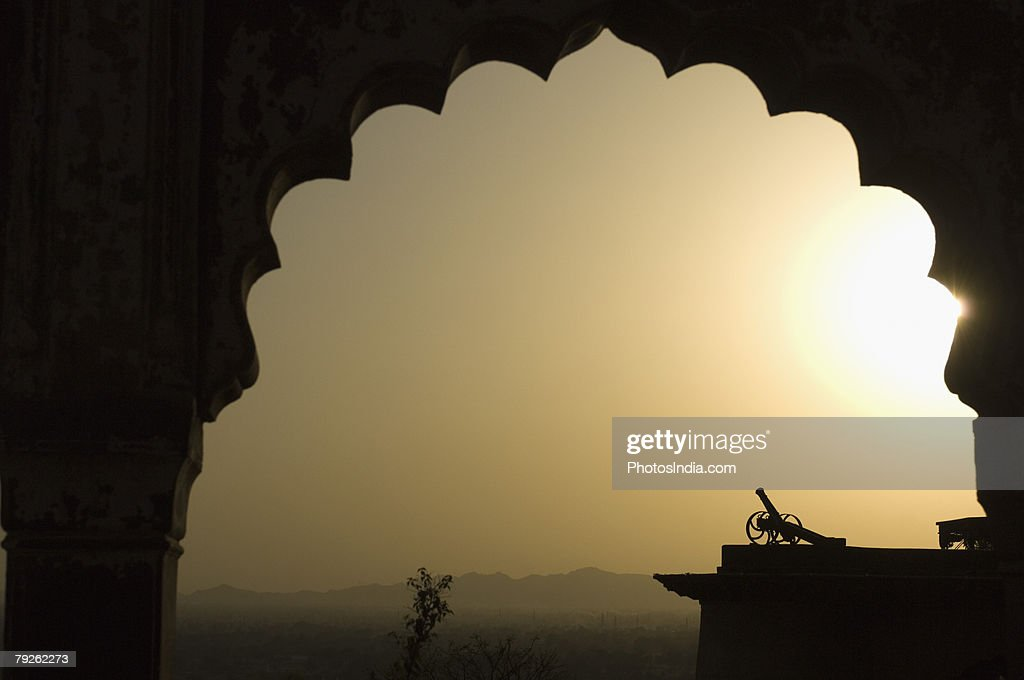 'Silhouette of a cannon viewed through an arch at sunset, Neemrana Fort, Neemrana, Alwar, Rajasthan, India' : Stock Photo