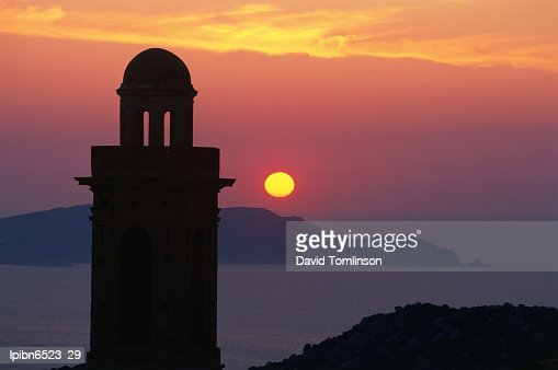 Silhouette of a church and the Punta della Revallata against a setting sun., Lumio, Corsica, France, Europe
