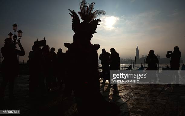 Silhouette of a costumed reveller posing in front of St George island during the Venice Carnival on February 8 2015 in Venice The 2015 edition of the...