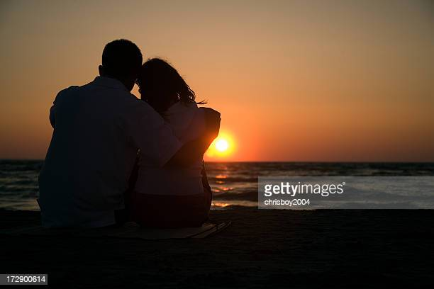 Silhouette of a couple on a beach watching the sun set