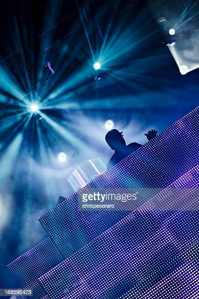 A silhouette of a DJ at a club