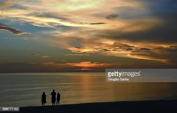 Silhouette of a family against a dramatic sunset on Marco Island, Florida, USA