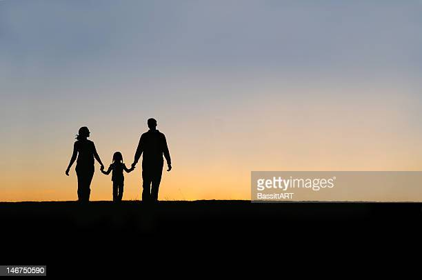 Silhouette of a family holding hands walking in the sunset